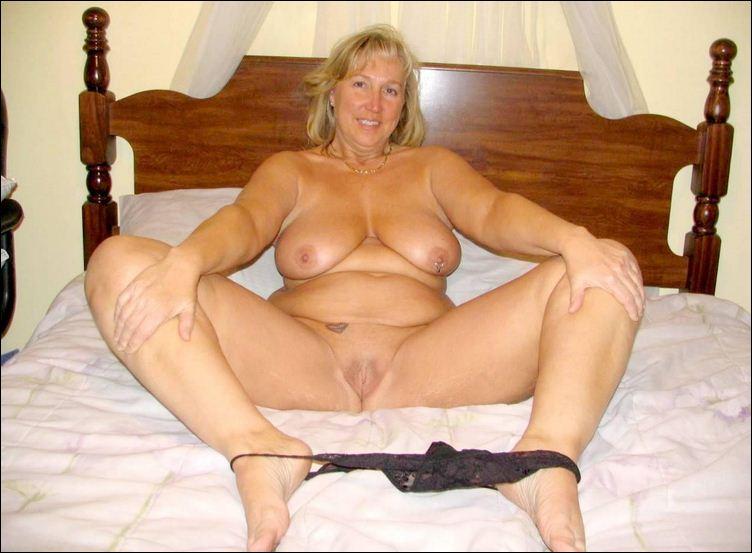 Толстая взрослая женщина на кровати раздвигает ноги